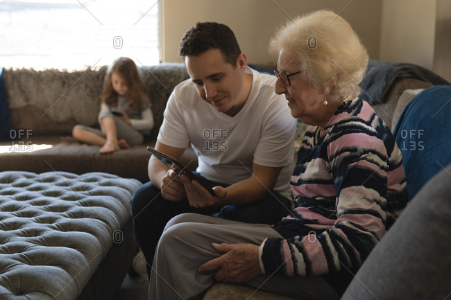 Mother and son using digital tablet on sofa in living room at home