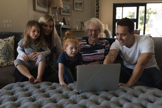 Multi generation family using laptop on sofa in living room at home