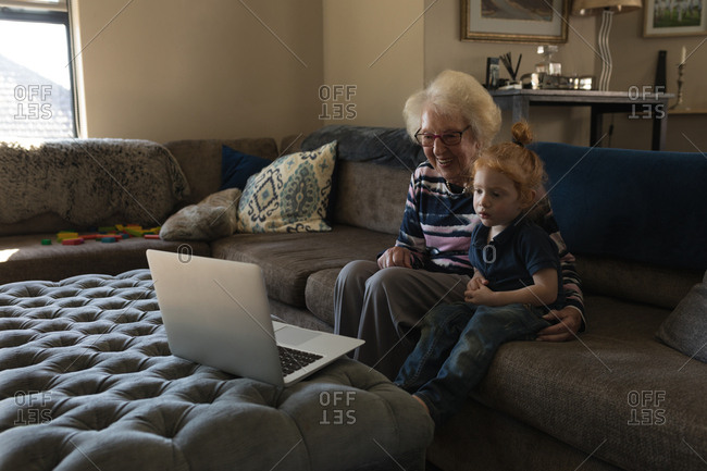 Grandmother and granddaughter making video call on laptop in living room at home