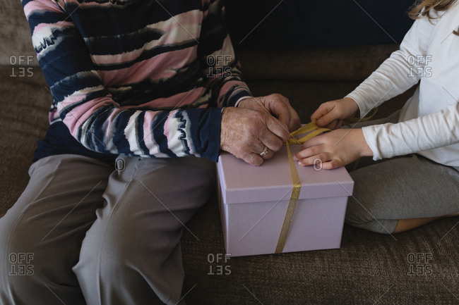 Mid section of grandmother and granddaughter opening gift box at home
