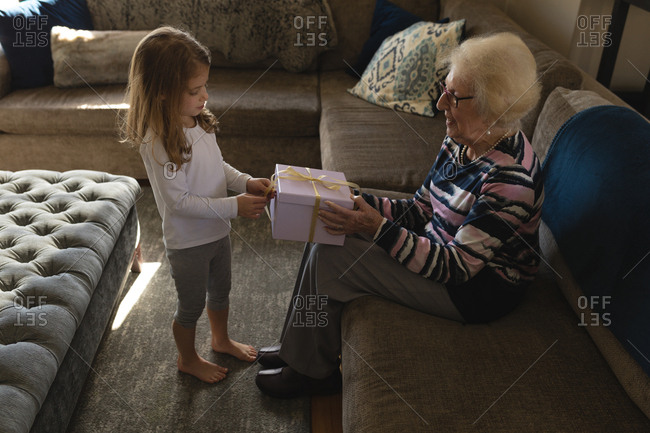 Granddaughter giving gift to grandmother in living room at home