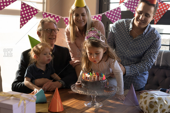 Multi-generation family celebrating birthday in living room at home