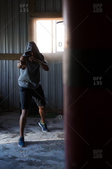 Determined male boxer practicing boxing in fitness studio