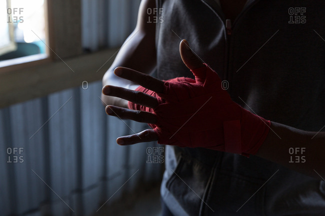 Close-up of male boxer tying hand wrap on hand in boxing club