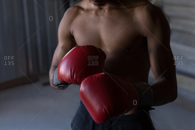 Mid section of male boxer practicing boxing in fitness studio