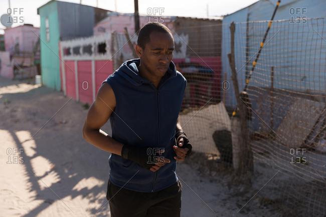 Male athlete jogging near village on a sunny day
