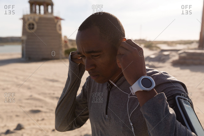 Male athlete wearing headphone near beach on a sunny day