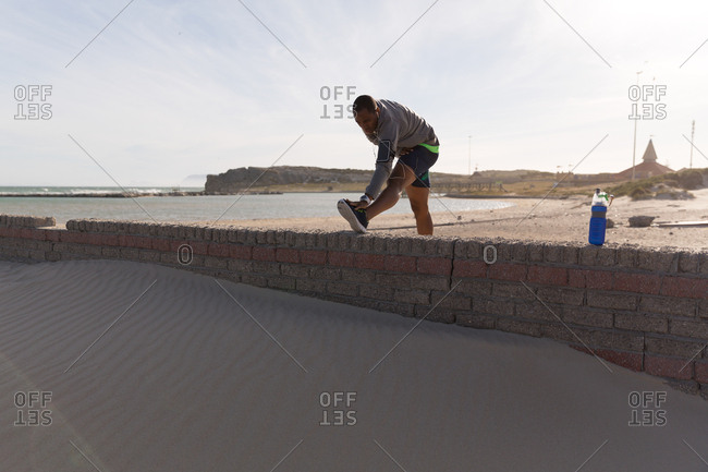 Male athlete stretching near beach on a sunny day