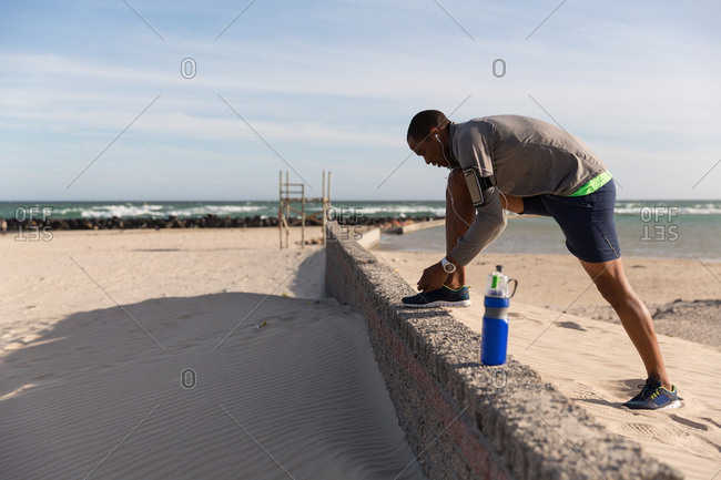 Male athlete tying his shoelaces on surrounding wall at beach