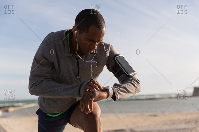 Male athlete checking his smartwatch while exercising near beach