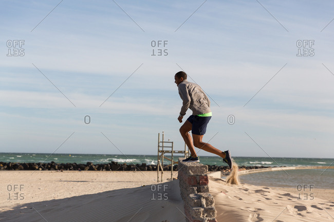 Male athlete exercising on surrounding wall near beach