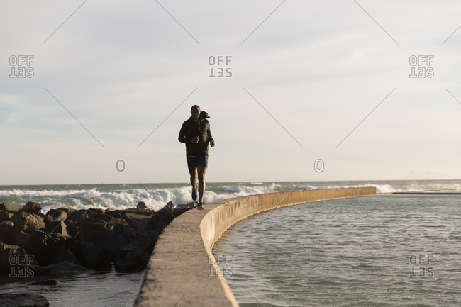 Male athlete jogging on surrounding wall on a sunny day
