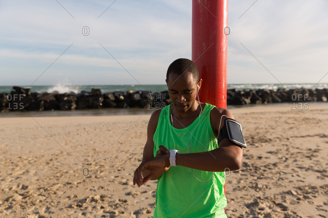 Male athlete using smartwatch near beach on a sunny day