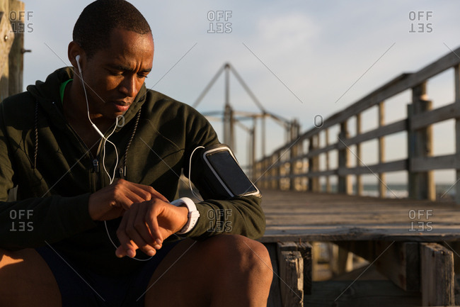 Male athlete using his smartwatch on pier at beach