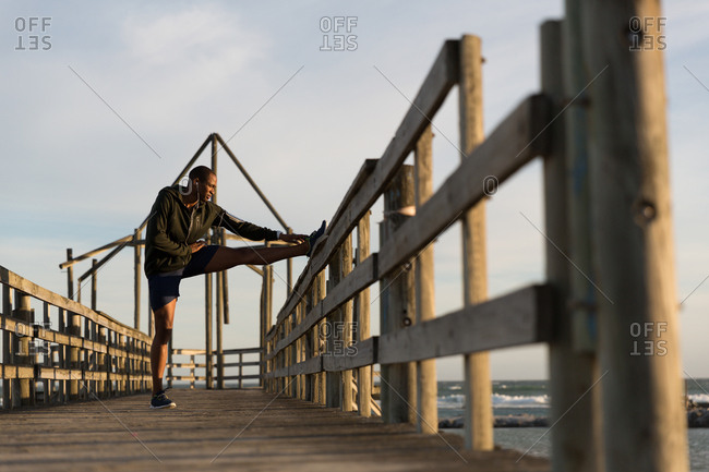 Male athlete stretching on pier at beach