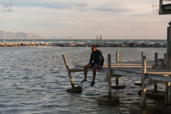 Male athlete sitting on pier at beach