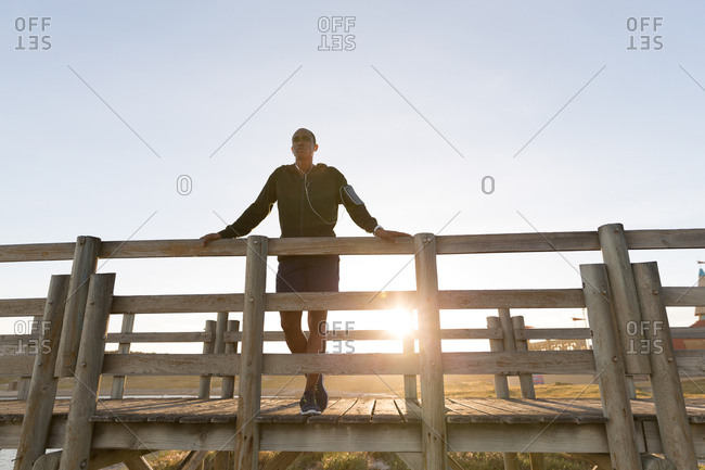 Low angle view of male athlete standing on pier