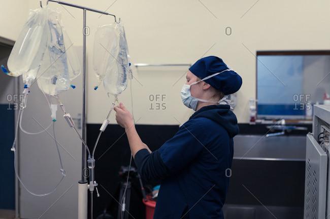 Female surgeon checking iv saline drop in hospital