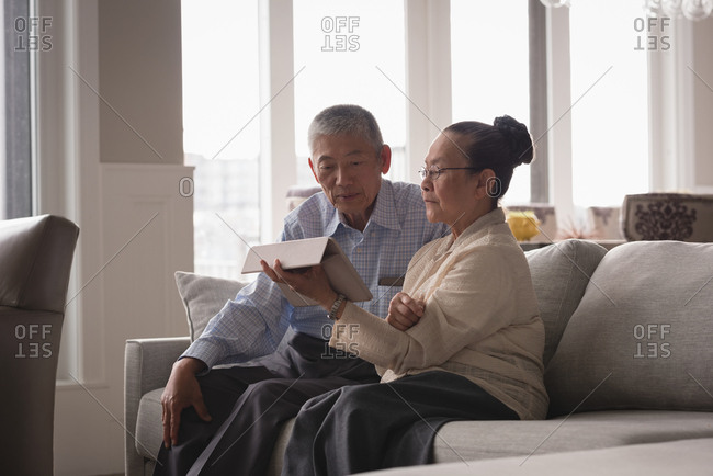 Senior couple discussing over a digital tablet on sofa in living room at home