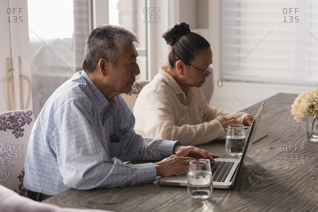 Senior couple using laptop and digital tablet on dining table at home