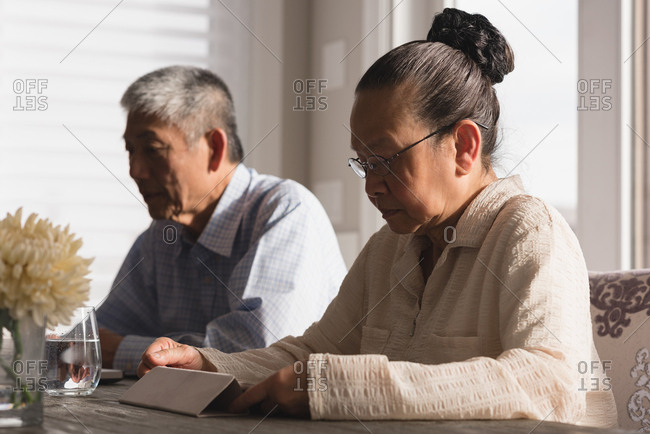 Senior woman using digital tablet on dining table at home