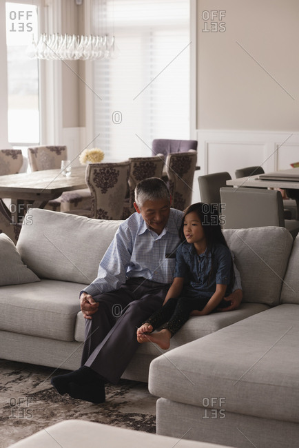 Grandfather and granddaughter interacting with each other on sofa in living room at home