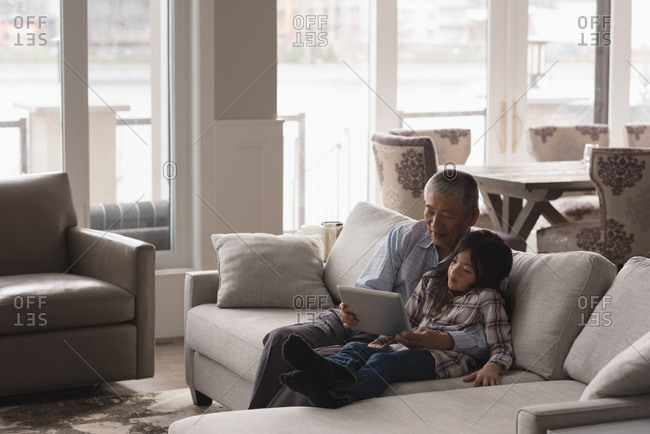 Grandfather and granddaughter using digital tablet on sofa in living room at home