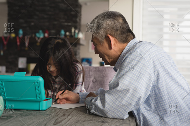 Grandfather and granddaughter drawing sketch on dining table at home
