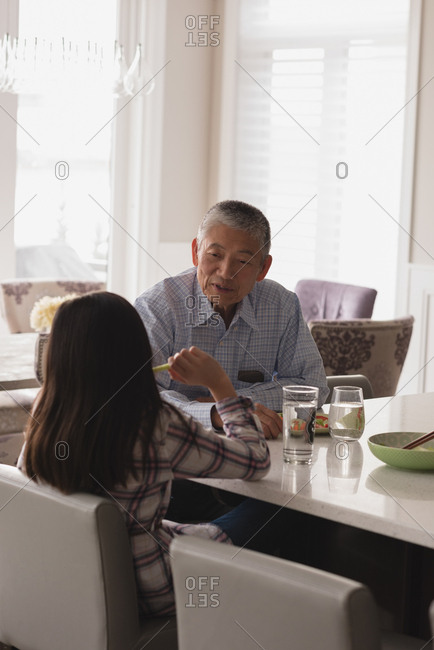 Grandfather and granddaughter interacting with each other on dining table at home