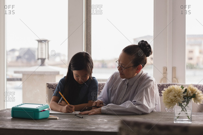 Grandmother and granddaughter drawing sketch on table at home