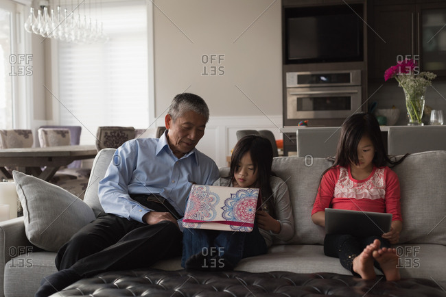 Grandfather and granddaughters using digital tablet on sofa in living room at home