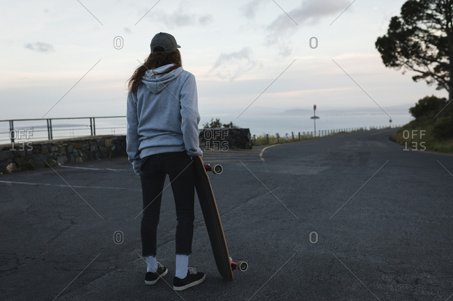 Rear view of skateboarder standing with skateboard on country road
