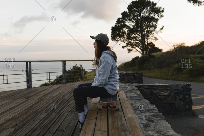 Side view of female skateboarder sitting on skateboard by railing at observation point