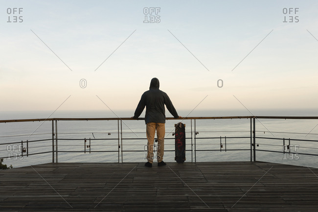 Rear view of male skateboarder standing by railing at observation point