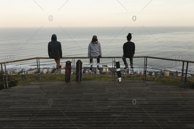Rear view of skateboarders sitting on railing at observation point