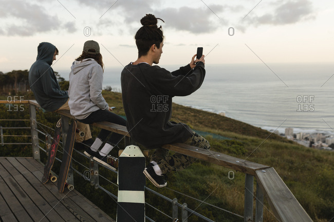 Side view of skateboarders sitting on railing at observation point