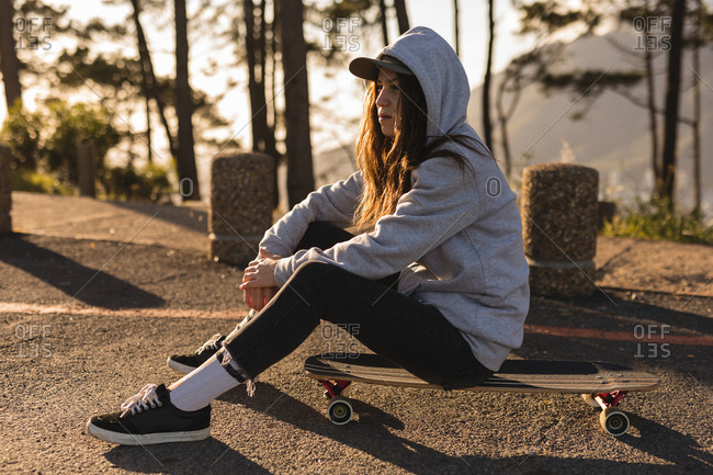 Thoughtful female skateboarder sitting on skateboard at country road