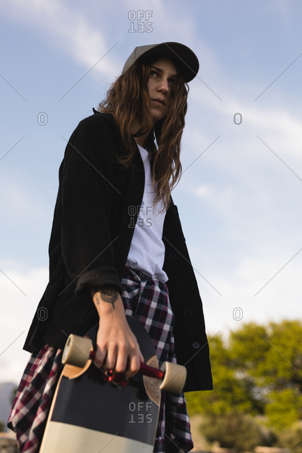 Low angle view of female skateboarder standing with skateboard