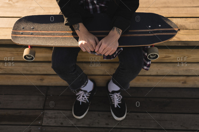 Low section of skateboarder sitting with skateboard on wooden bench