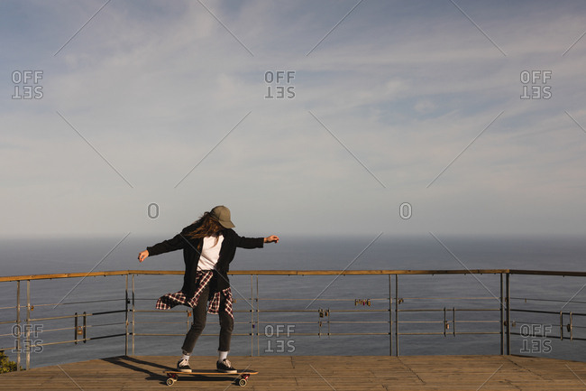 Female skateboarder skating on observation point