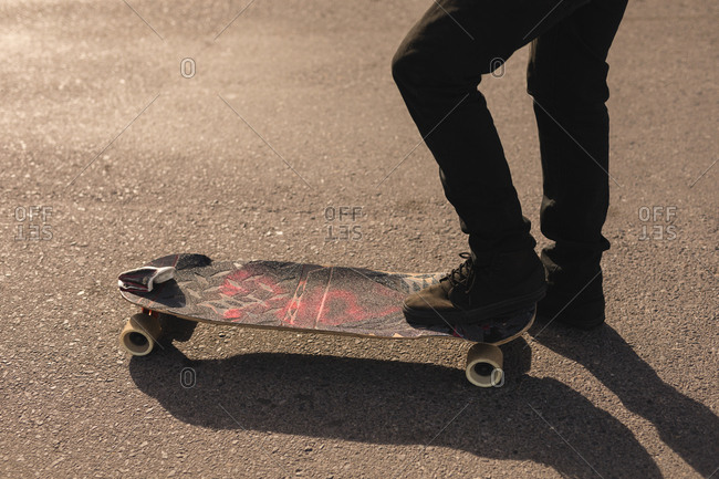 Close-up of skateboarder skating on country road