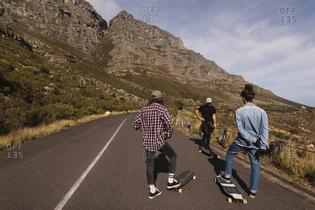 Rear view of skateboarders standing with skateboard on downhill at countryside