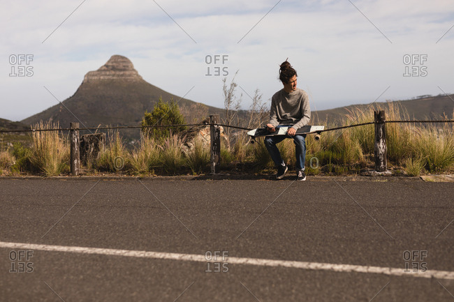 Young male skateboarder sitting on downhill at countryside