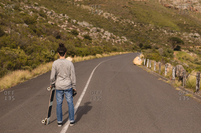 Rear view of skateboarder standing with skateboard on downhill at countryside