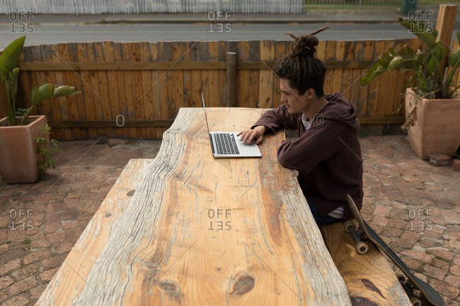 Young male skateboarder using laptop at outdoor cafe