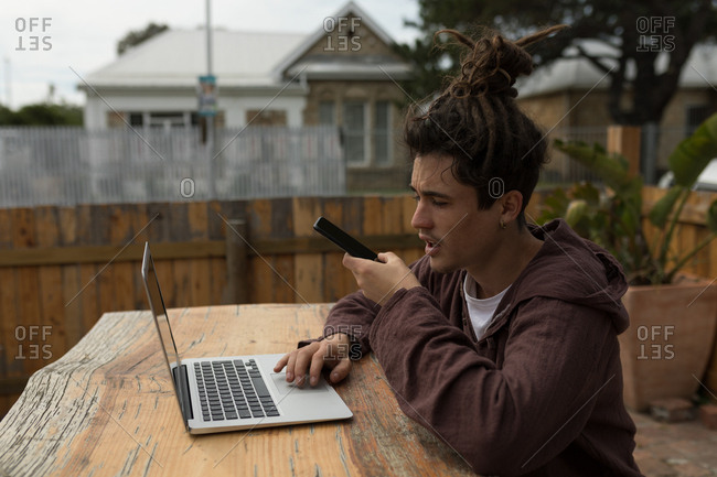 Young male skateboarder talking on mobile phone while using laptop