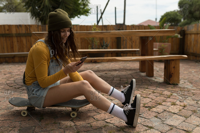Stylish female skateboarder using mobile phone while sitting on skateboard