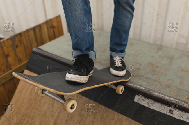 Low section of skateboarder standing with skateboard on skateboard ramp at skateboard court