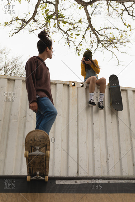 Young female skateboarder clicking photo while male skateboarder skating on skateboard ramp