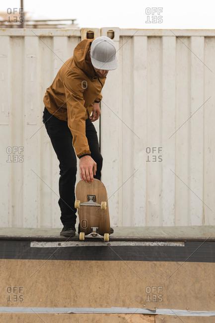 Stylish male skateboarder skating on skateboard ramp at skateboard court
